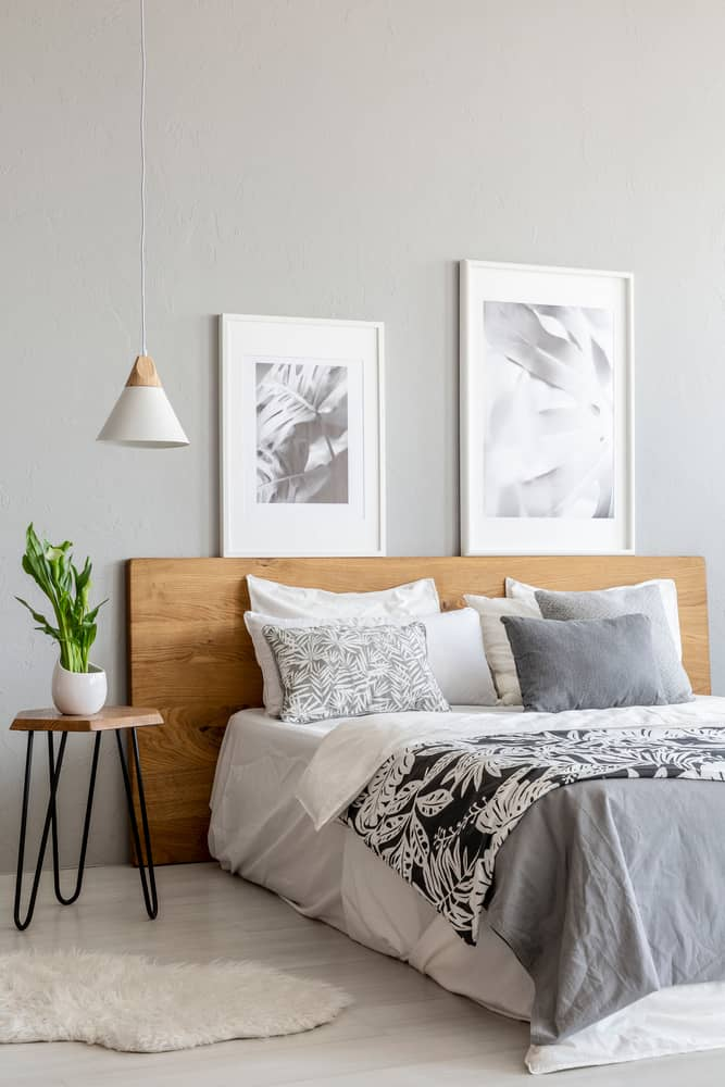 a decluttered minimalistic gray bedroom with a bed and nightstand and rug