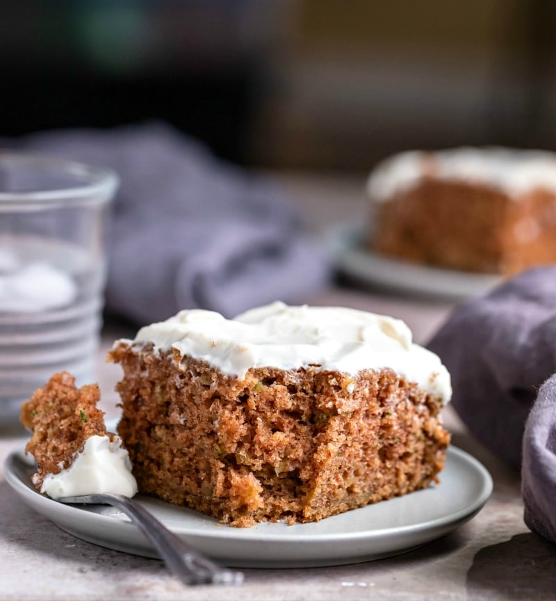 spiced zucchini cake with cream cheese frosting on plate