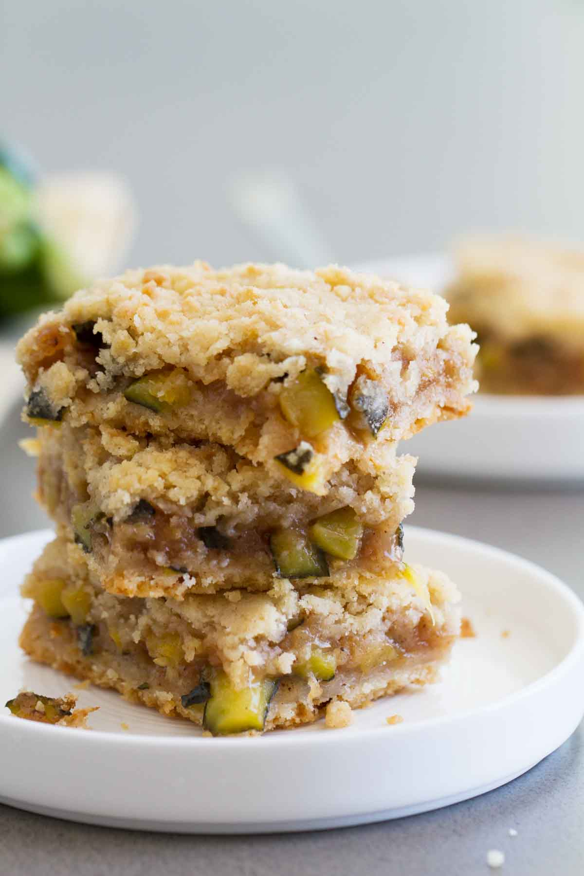 zucchini cobbler bars stacked on white plate