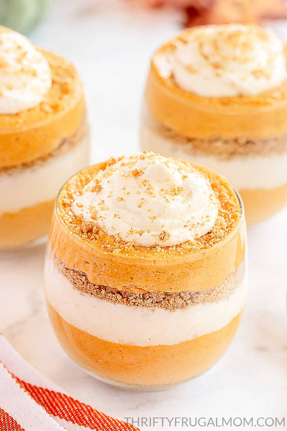 no bake pumpkin cheesecake trifles in glass cups on a white table