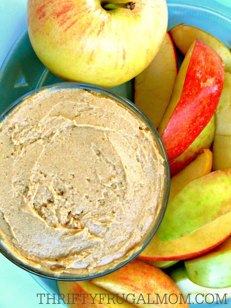 cheap healthy snack of peanut butter yogurt fruit dip in a bowl with sliced apples beside it