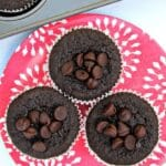 2 flourless chocolate muffins with chocolate chips on top on a pink plate