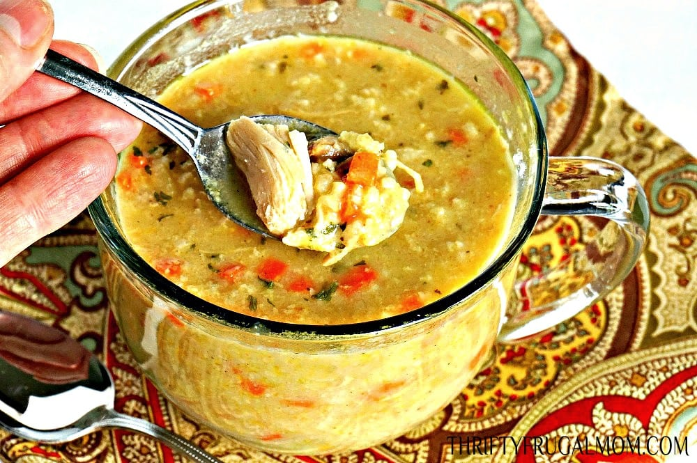 Curry Chicken and Rice Soup being spooned out of a large glass mug