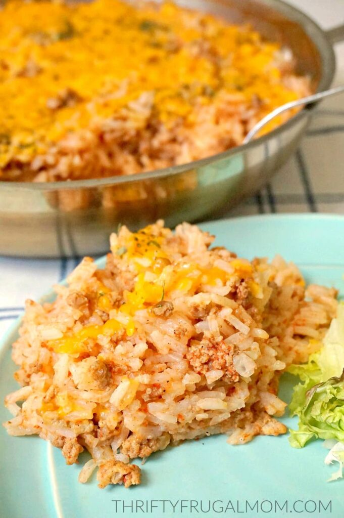 speedy Spanish rice on an aqua plate with a skillet full in the background