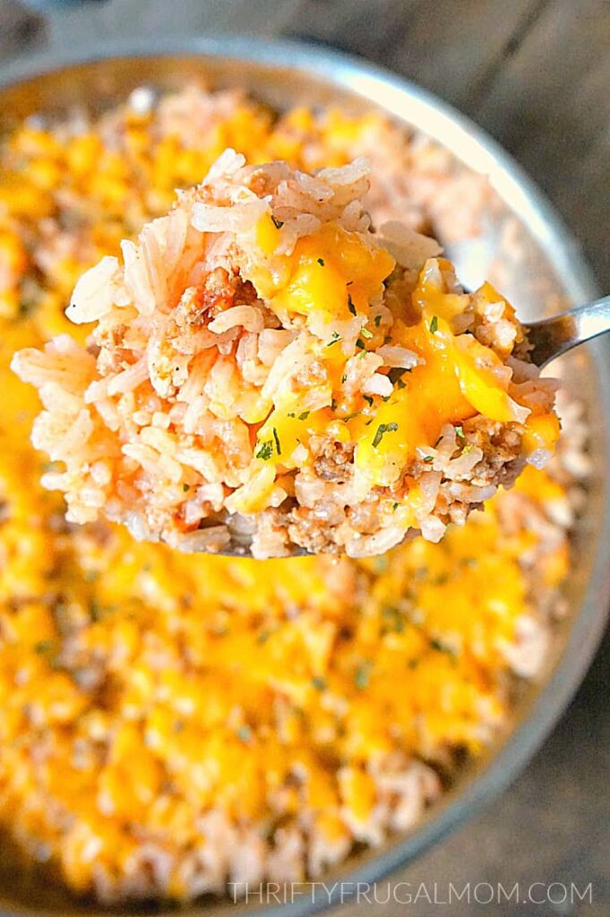 a close up of Speedy Spanish Rice with Ground Beef Skillet being spooned out of a pan