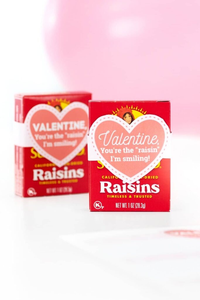 two boxes of raisins with a paper heart on them saying Valentine your the raisin I'm smiling