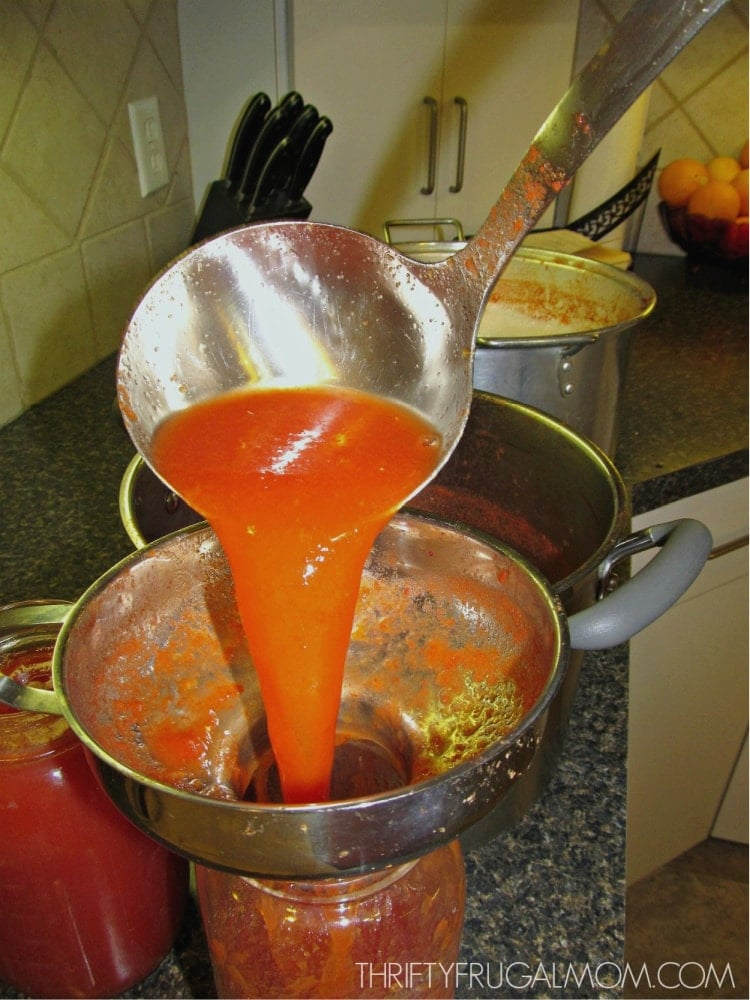 homemade tomato juice being poured into canning jar