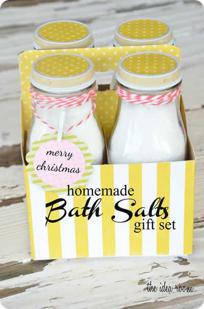 four jars of bath salts in a yellow and white striped box