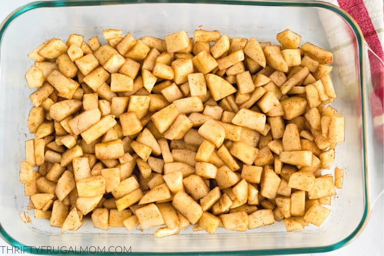 diced apple tossed in cinnamon sugar in a baking dish