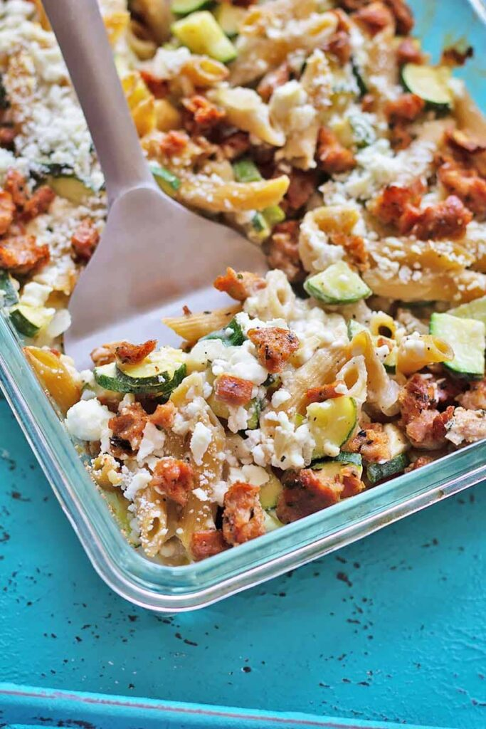 an easy healthy dinner of Baked Penne Sausage and Feta casserole in a clear glass baking dish on an aqua table