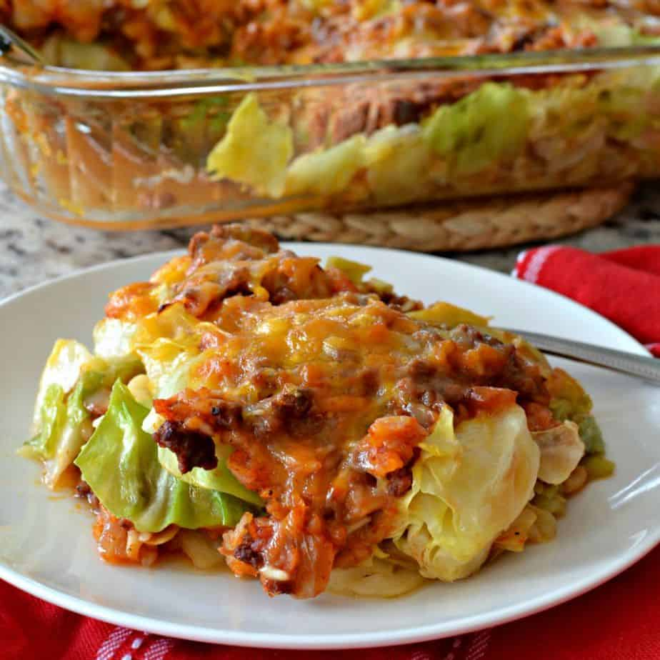 a serving of cabbage roll casserole on a white plate with the casserole dish in the background