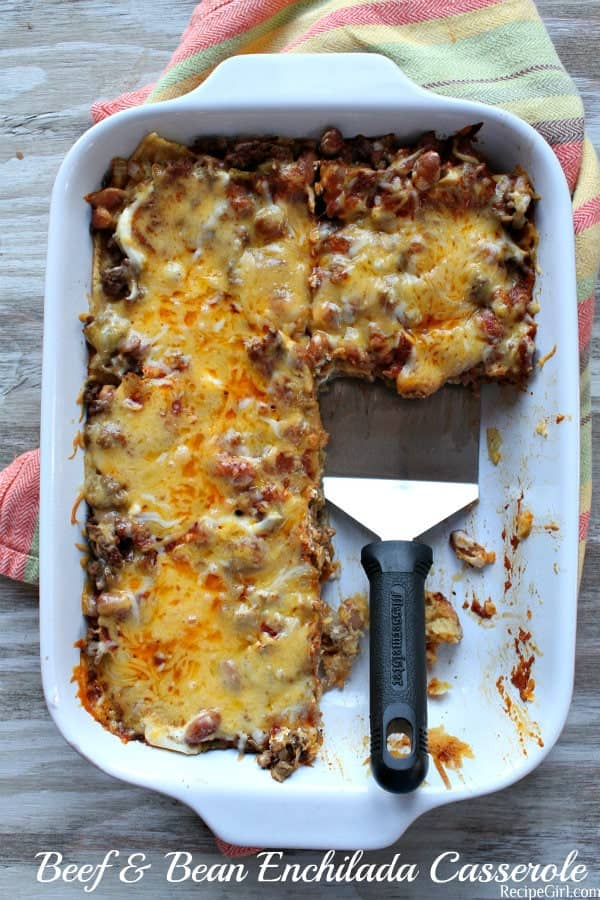 Beef and Bean Enchilada Casserole in a white baking dish, with a serving spoon- a cheap dinner