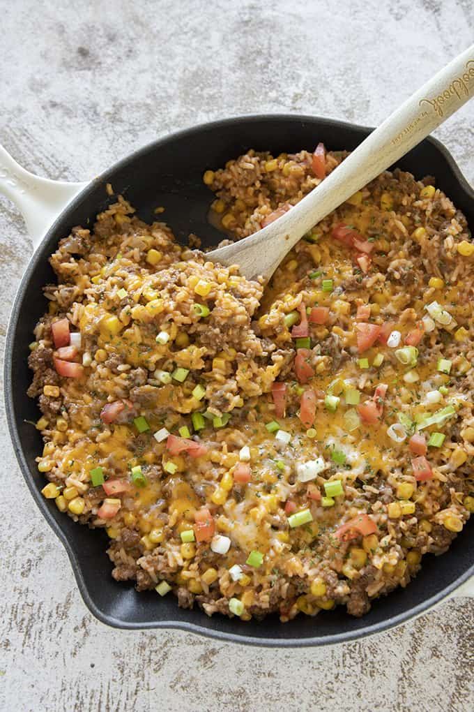 Cheap dinner recipe of One Pan Mexican Rice Casserole in a cast iron skillet with a wooden spoon