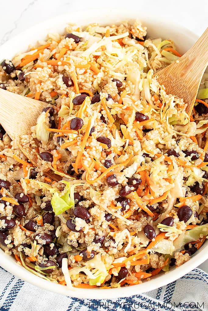 Easy Quinoa Cabbage Salad with beans and carrots in a white bowl with wooden spoons resting it it