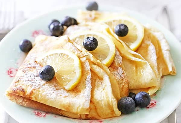 a simple breakfast recipe bisquick crepes on a white plate with blueberries and lemons