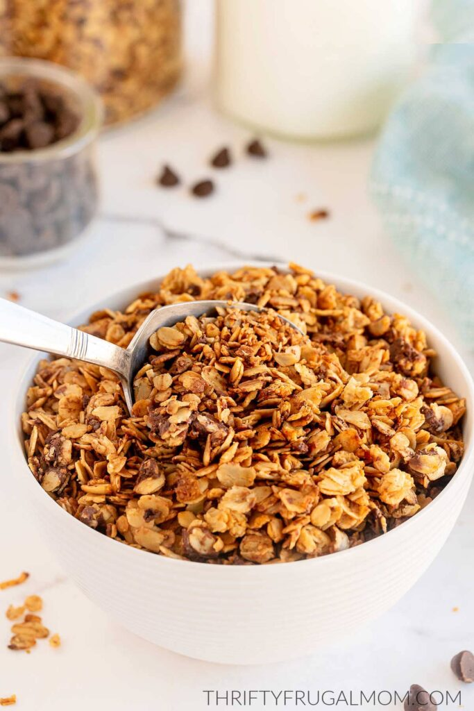 a white bowl full of chocolate granola with chocolate chips in the background