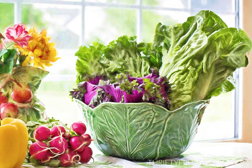 a bowlful of lettuce on a table with radishes and a pepper