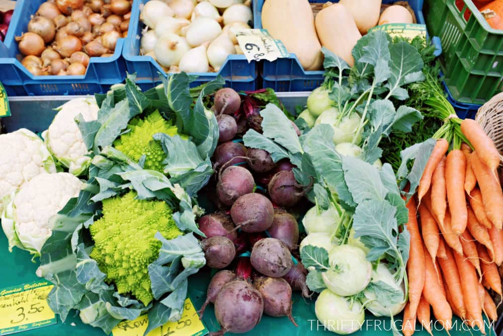 a variety of fresh vegetables piled together at a market stand