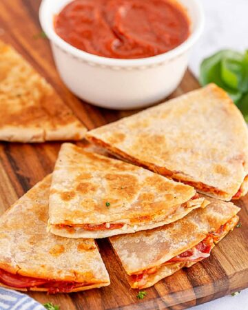 pepperoni pizza quesadillas on a wooden table with pizza sauce