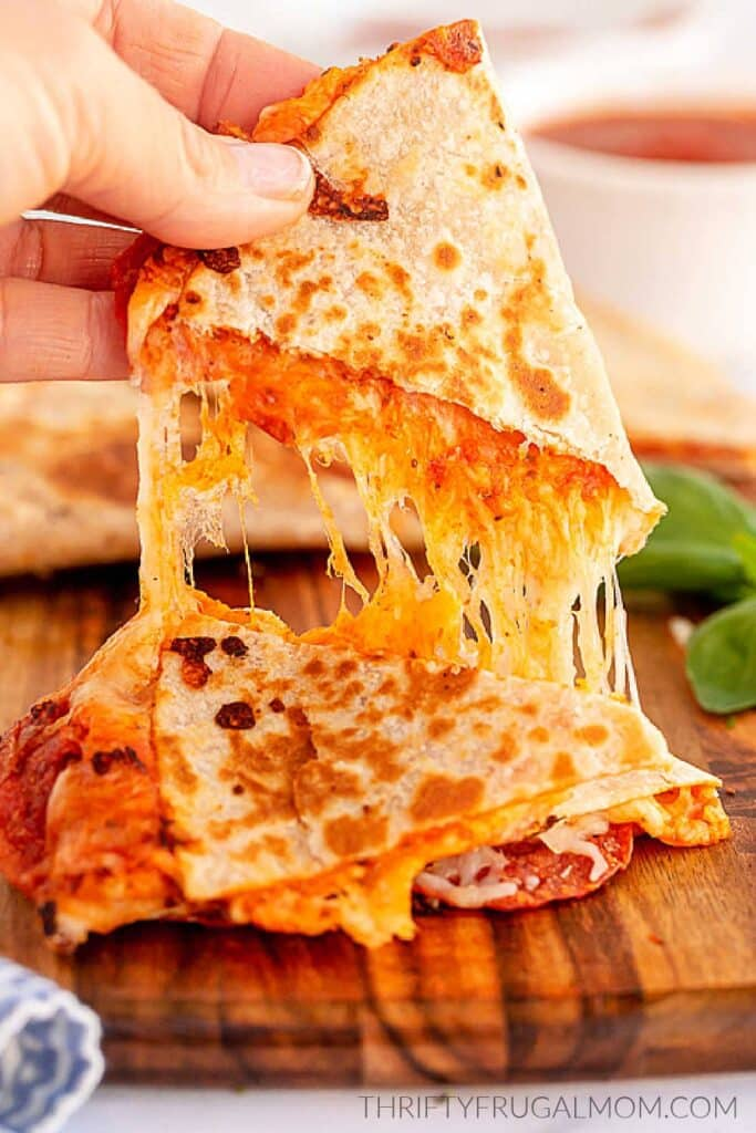 pizza quesadillas being pulled apart with melted cheese stringing between them
