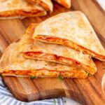 3 pepperoni pizza quesadillas stacked on a wooden cutting board